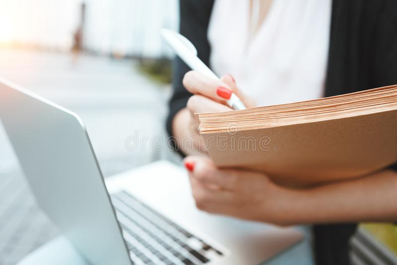 Business woman work during the lunch break use modern laptop and paper documents. Young female student prepares for a thesis sits on outdoors in urban space royalty free stock photo