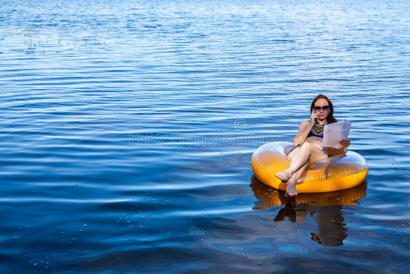 Business woman workaholic working sitting in an inflatable ring on the sea during the holidays, free space. royalty free stock image