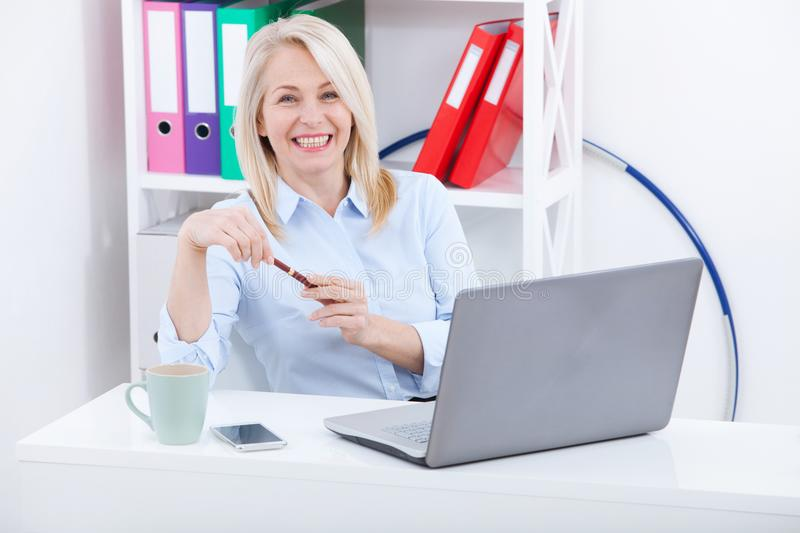 Business woman working on a aptop. Chatting with the client online via chat. Stormy emotions express delight. stock image