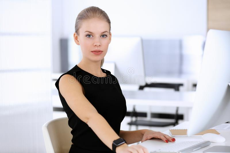 Business woman working with computer while sitting at the desk in modern office. Secretary or female lawyer looks stock photos
