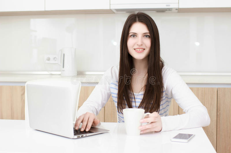 Business woman working from her home. Multitasking. Having morning coffee while texting on the smarth phone and working on leptop computer royalty free stock images