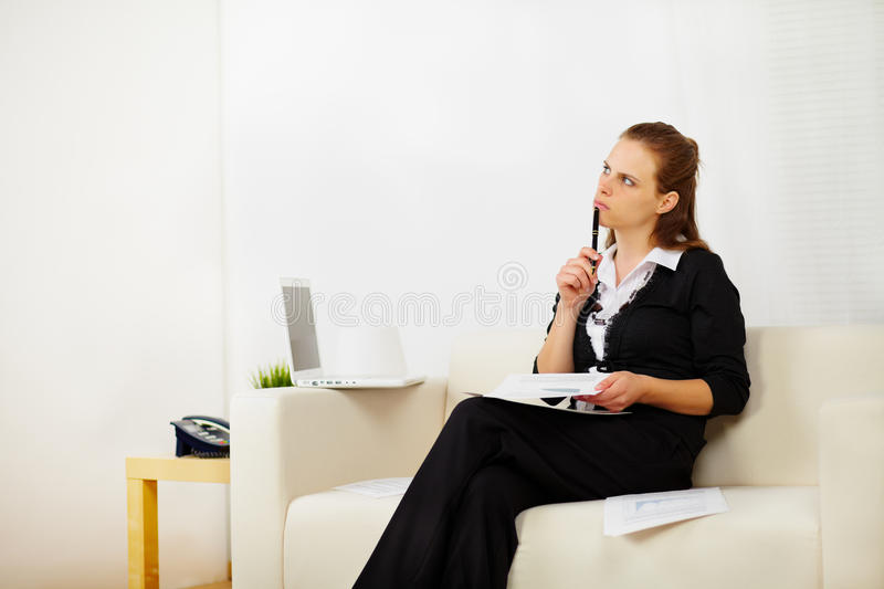 Business woman working at home. Portrait of a pretty business woman working at home and looking up while she is thinking royalty free stock images