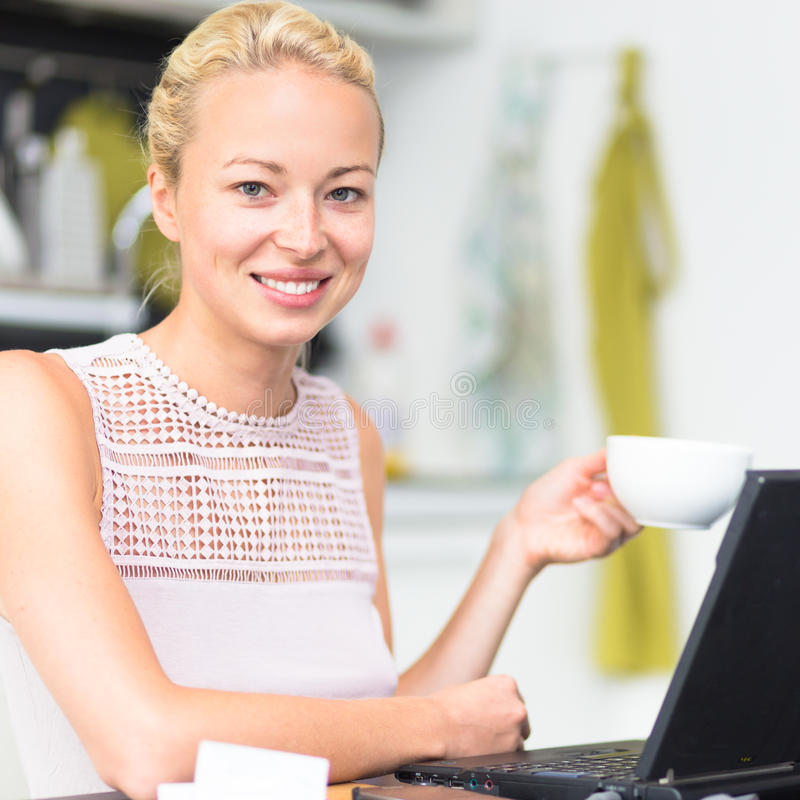 Business woman working from home. Happy business woman working from her home having more time for her family and her morning coffee stock image