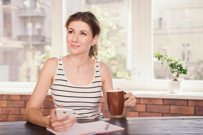 Business woman working at home office. Young woman drinking coffee and typing message on her mobile phone while sitting at her desk stock photography