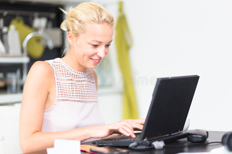 Business woman working from home. Business woman working remotly from her dining table. Home kitchen in the background stock photography