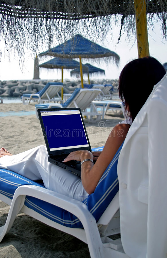 Business woman working on a laptop on the beach royalty free stock images