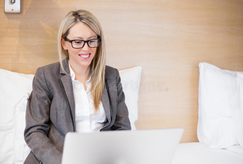 Business woman working with laptop computer in bed royalty free stock images