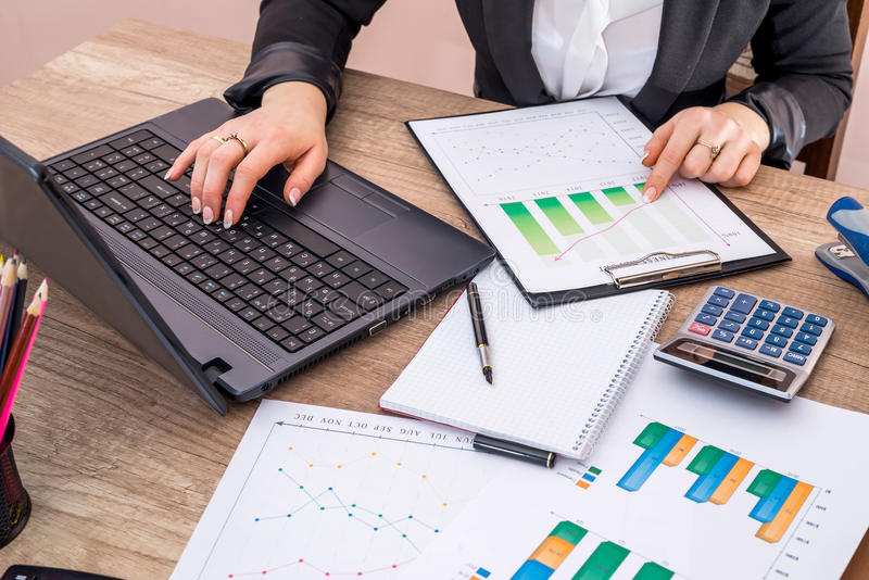 Business woman working with laptop, graph, pen and notebook in office. stock photos