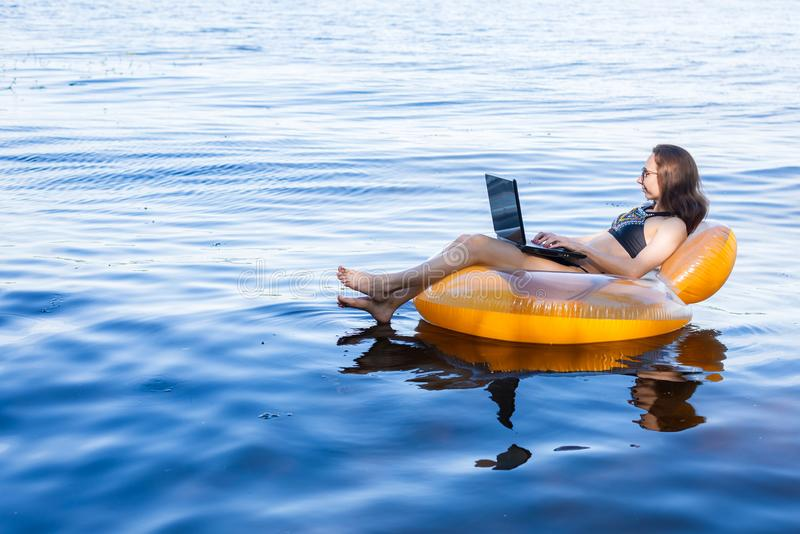 Business woman working on a laptop in an inflatable ring on the sea, the concept of working on vacation. royalty free stock photography