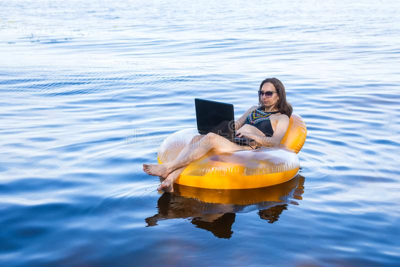 Business woman working on a laptop in an inflatable ring on the sea, the concept of working on vacation. stock photography