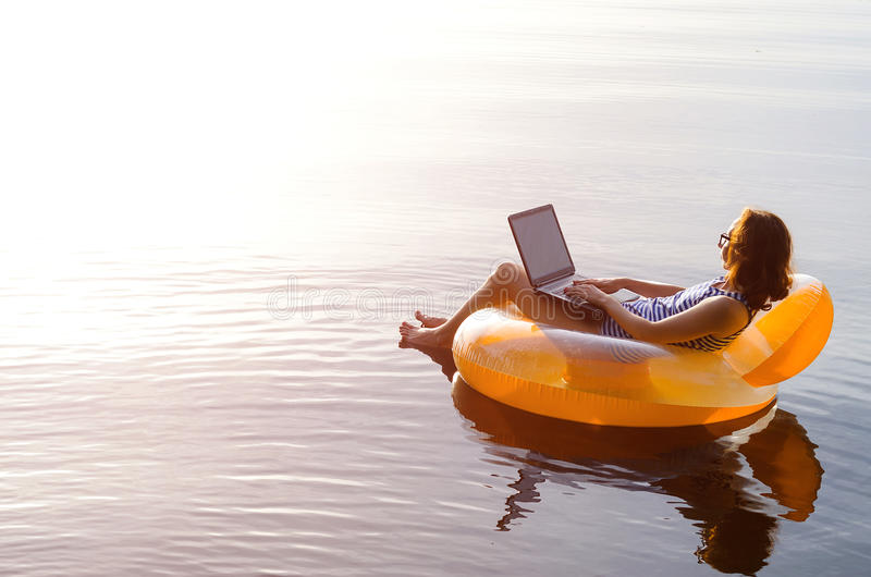 Business woman working on a laptop in an inflatable ring in the. Water, a copy of the free space. Workaholic, work on vacation royalty free stock photography
