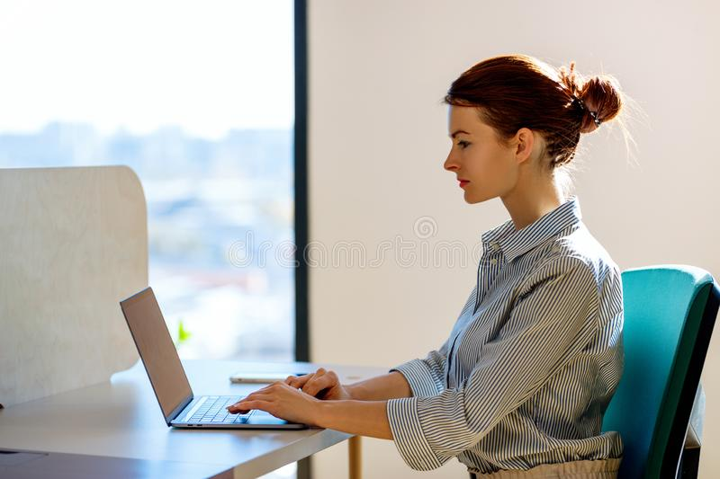 Business woman working on laptop in the office. stock image