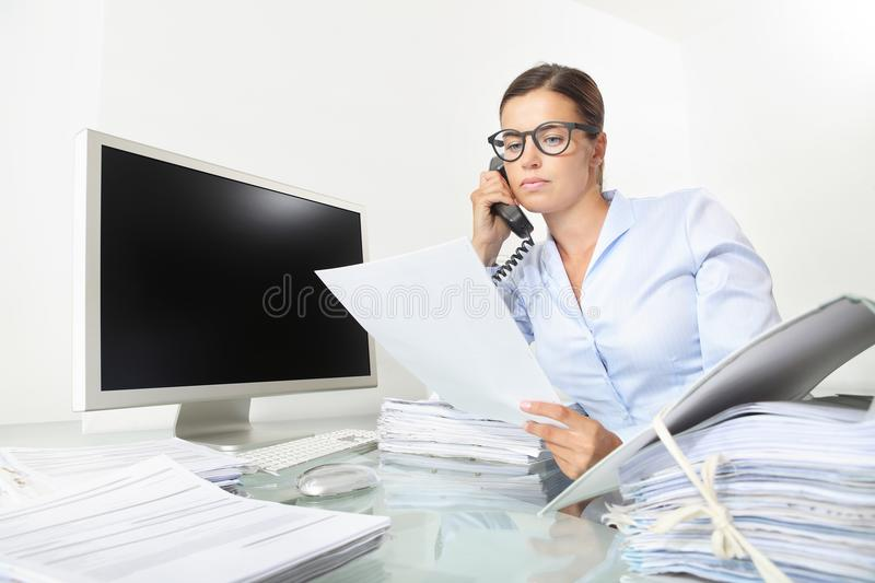business woman working at office desk with computer reads a documents and speak on the phone, isolated on white background stock image