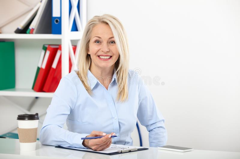 Business woman working in office with documents. Beautiful middle aged woman looking at camera with smile while siting royalty free stock photo