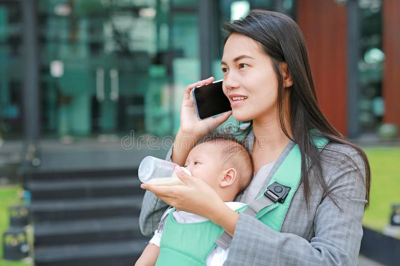 Business woman working by telephone with carrying her infant and feeding her child`s by milk bottle. Busy mother hurrying. royalty free stock photos