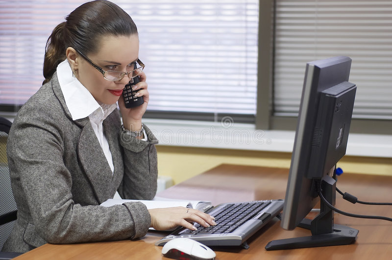 Business woman works behind the computer. The young business woman behind a workplace royalty free stock photography