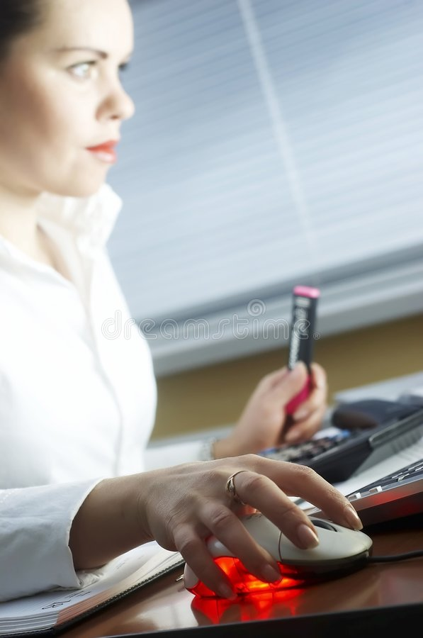 Business woman works evening at office. Beautiful girl in the evening sits at office royalty free stock image