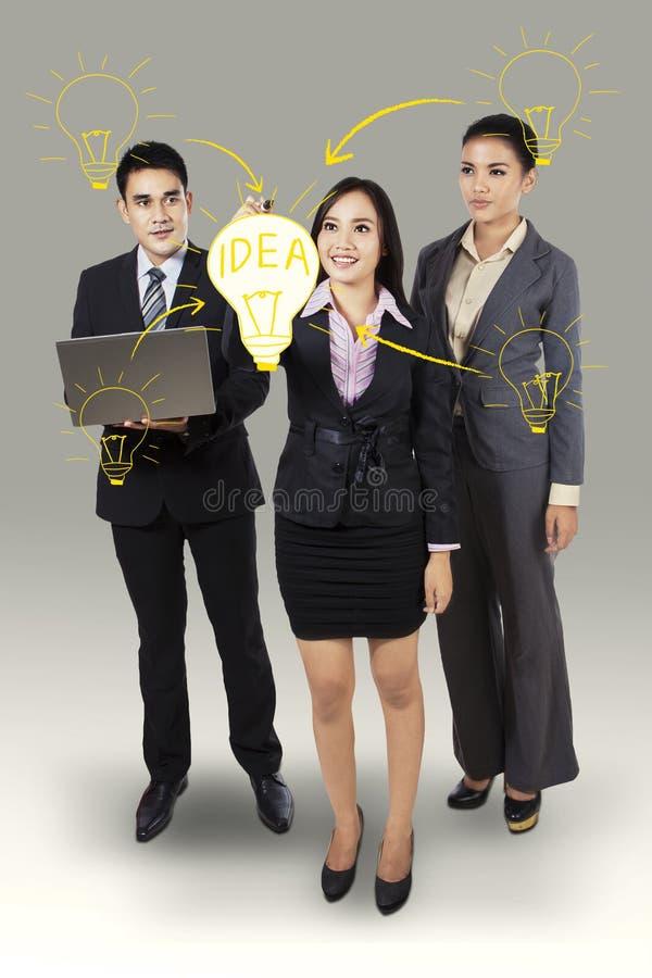 Business woman writing big idea. Business women writing big idea with her business team royalty free stock photo