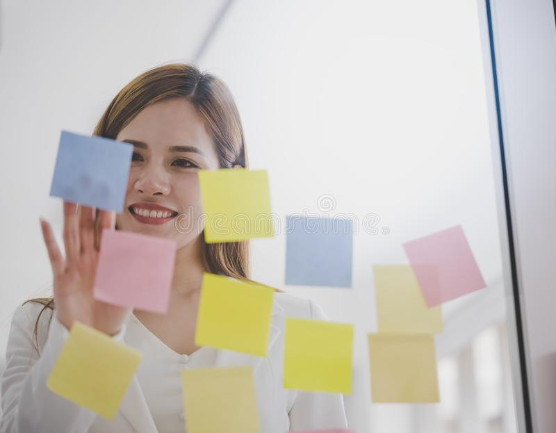 Business woman writing idea on to post it windows for plan. Business woman is writing idea on to post it windows for plan stock photos