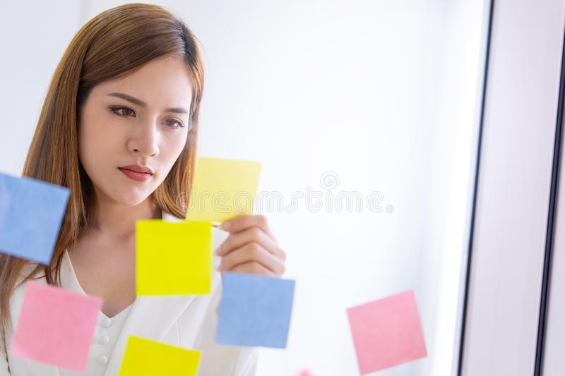 Business woman writing idea on to post it windows for plan. Business woman is writing idea on to post it windows for plan royalty free stock images