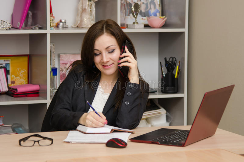 Business woman writing in a notebook and talking on phone. Cute business woman in the office at the computer royalty free stock images