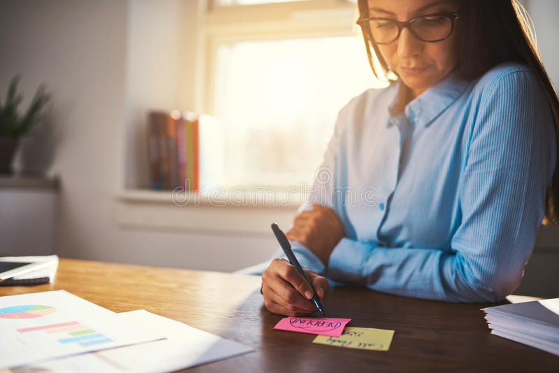 Business woman writing notes on post it royalty free stock images