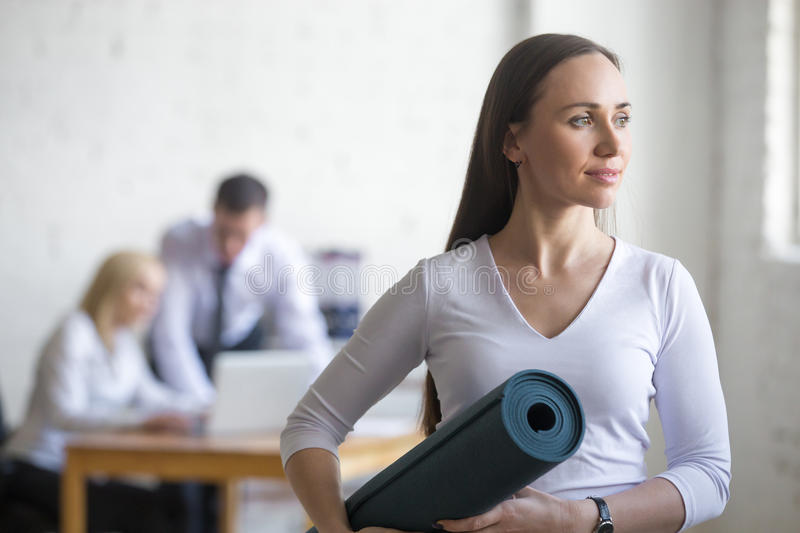 Business woman with yoga mat. Business and healthy lifestyle concept. Portrait of beautiful sporty young office women standing with yoga mat at workplace on royalty free stock photos