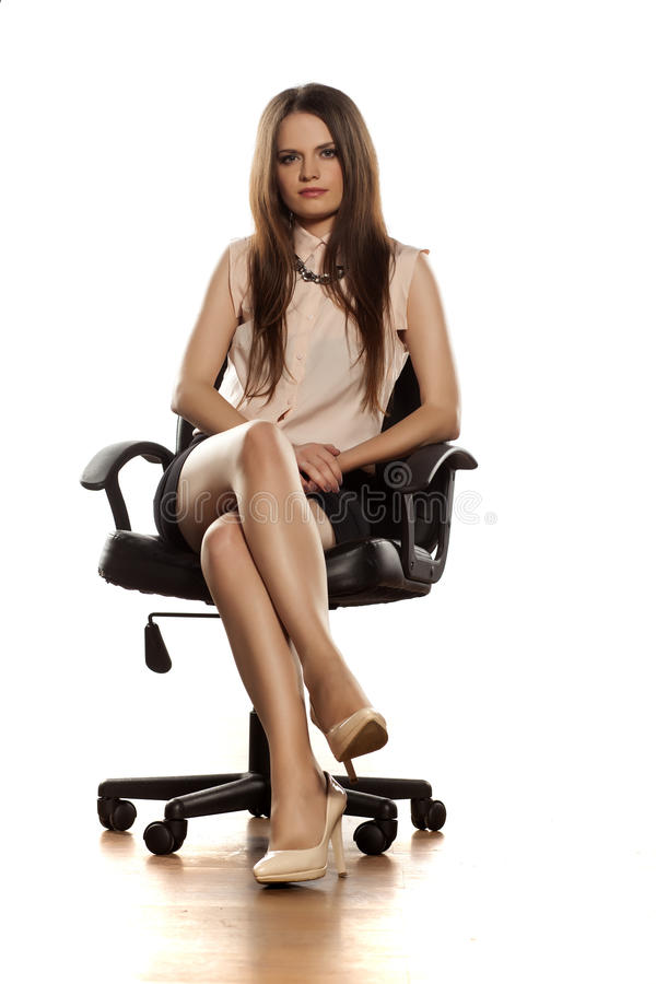 Business woman. Young business woman sitting in a office leather chair with crossed legs royalty free stock photography
