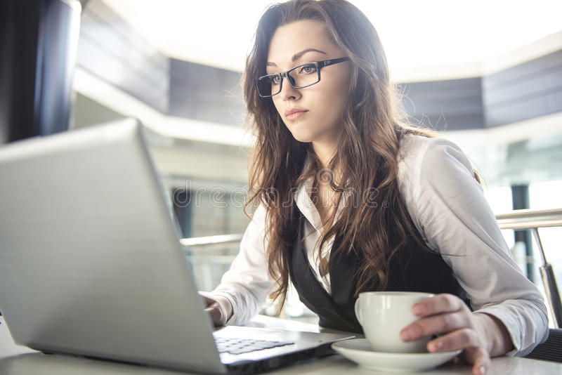 Business woman. Young business woman working for a laptop with a cup of coffee in a modern office stock photography
