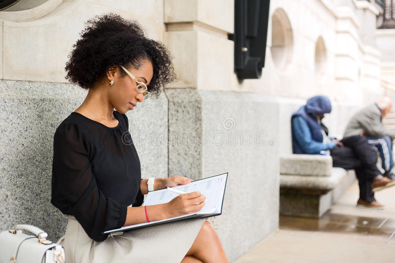 Business woman. Young business woman writing in her diary stock photography