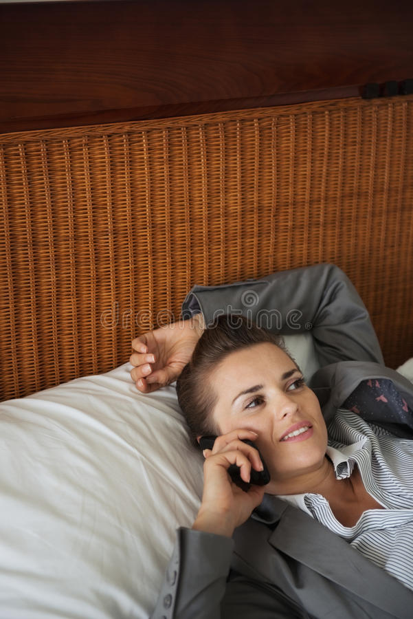 Business womanin hotel room talking cell phone. Business woman laying on bed in hotel room and talking cell phone royalty free stock image