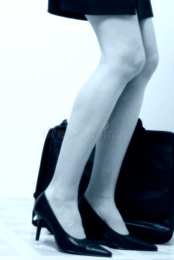 Business womans legs beside briefcase royalty free stock photo