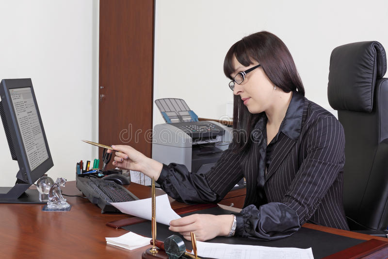 Business women. The young woman the chief works at office behind a table royalty free stock images