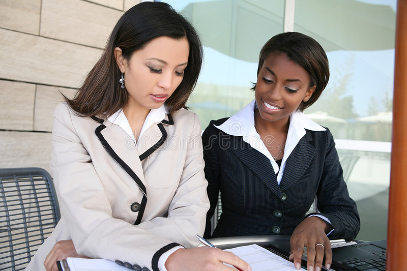 Business Women. An attractive women business team working with computer stock image