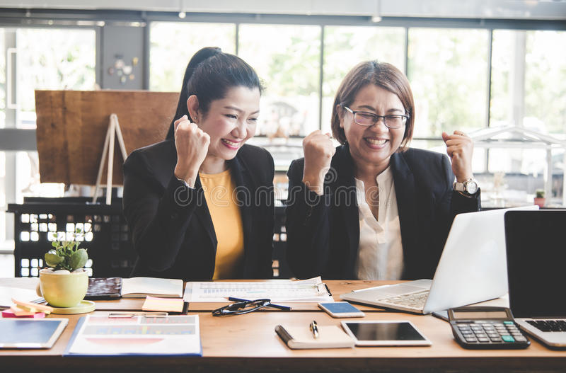 Business women celebrating good project results royalty free stock photo