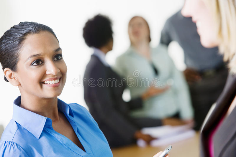 Business Women Communicating With Each Other. Happy multi ethnic business women communicating with each other with colleagues discussing in the background royalty free stock image