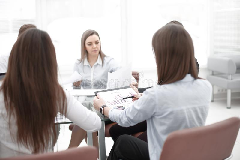 Business woman discusses with the business team financial success of the company. Business women discusses with the business team financial success of the royalty free stock images