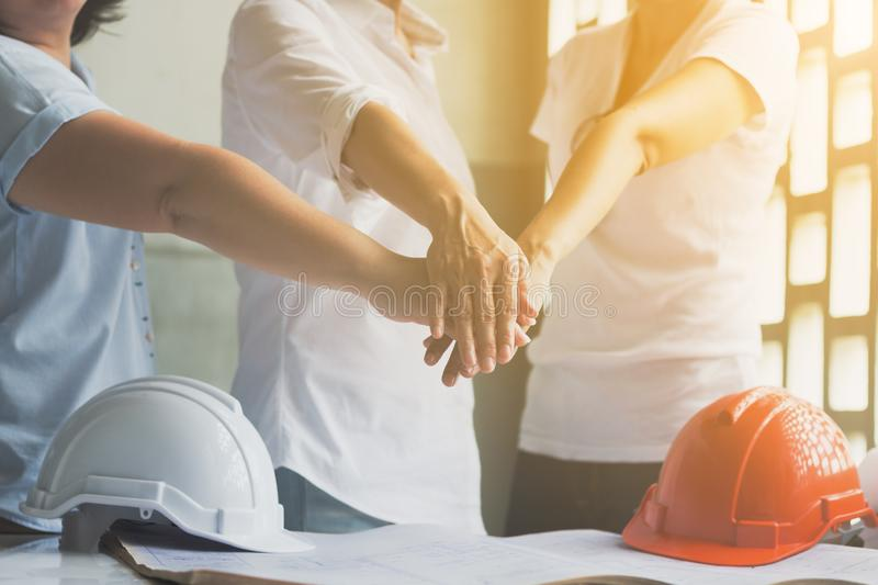Business women and engineer working hands of business people joined hands together in office meeting. Teamwork Concept and stock images