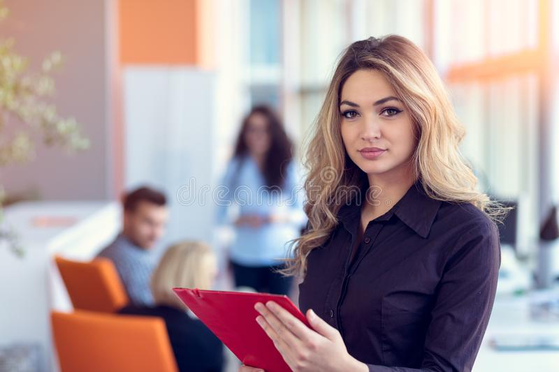Business woman with folders standing and team mates working in meeting room at office. Business women with folders standing and team mates working in meeting stock image