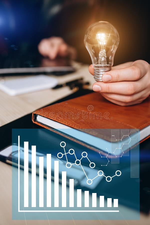 Business women hand holding light bulb, concept of new ideas with innovation and creativity. Concept of virtual diagram,graph stock photography