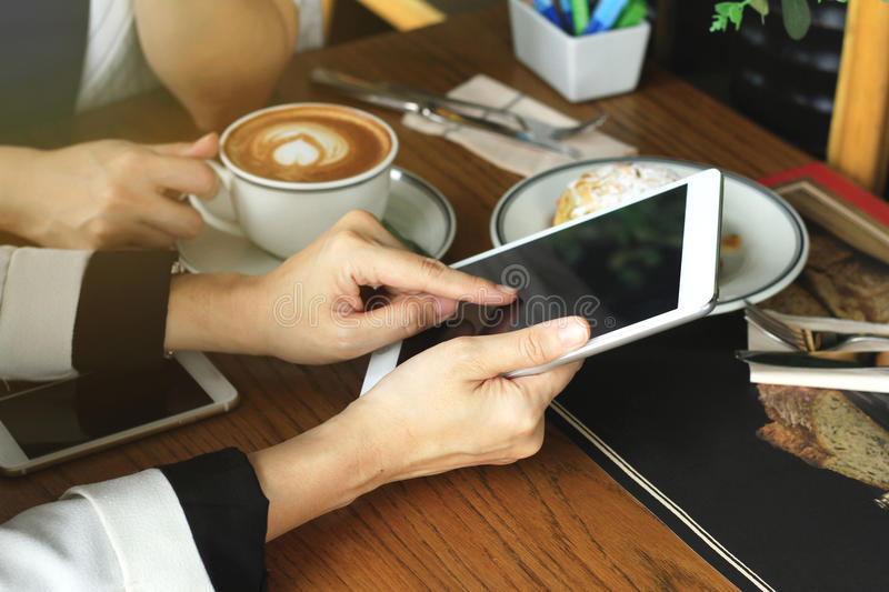 Business women looking at the tablet computer, Colleagues discussing business at cafe, Everywhere is a working place concept. Blank screen for mock up stock photography