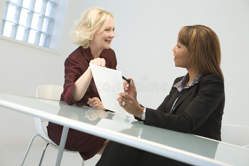 Business Women in Meeting. Two business women in a meeting discussing a contract royalty free stock photos