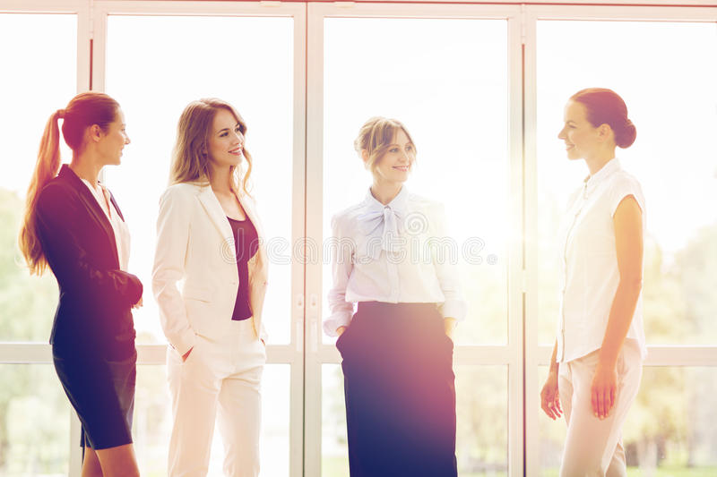 Business women meeting at office and talking. People, work and corporate concept - business women meeting at office and talking stock photo
