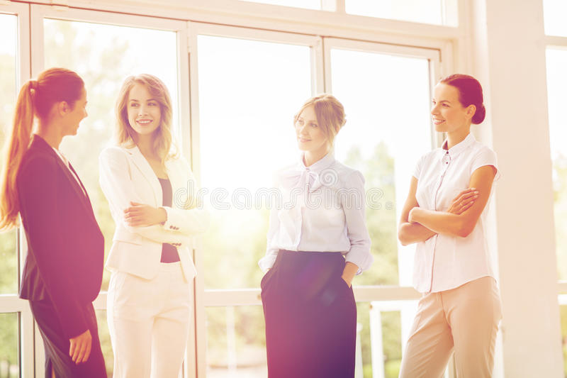 Business women meeting at office and talking. People, work and corporate concept - business women meeting at office and talking royalty free stock image