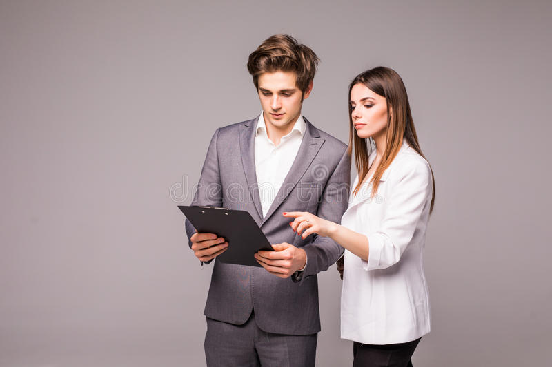 Business woman and business man pointing finger at blank isolated on gray background royalty free stock photos