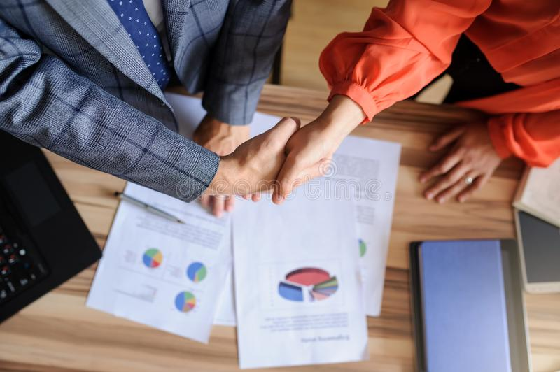 A business woman and man at a  office desk  handshaking, only hands stock photography