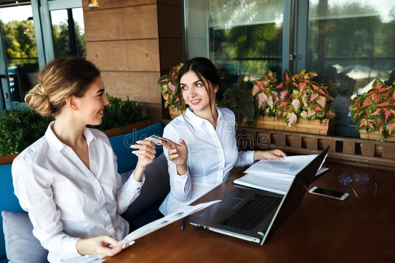 Business women partners are working in a cafe and completing the deal.  Woman passes a credit card royalty free stock photo