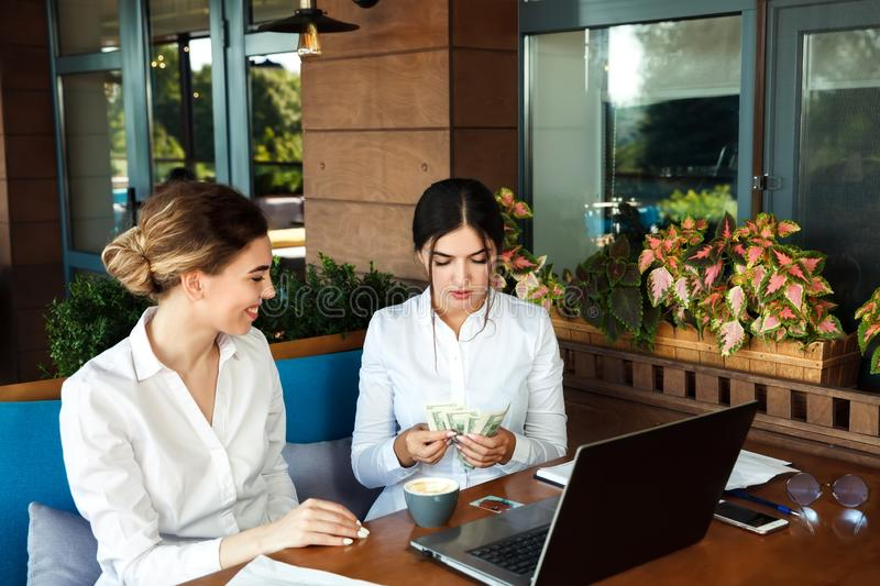 Business women partners are working in a cafe and counting money royalty free stock photography