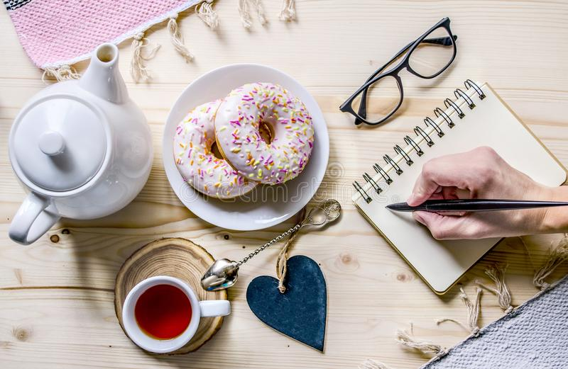 Business women`s composition with tea and donuts. Snack at the desk. Office table desk. Home office workplace. Top view. Copy space. Mock-up stock photos