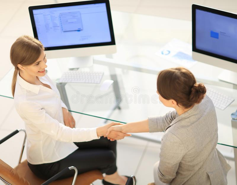 View from the top.business woman shakes hands with the officer sitting near the desktop royalty free stock photo